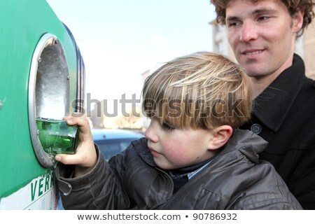 Little boy putting a glass bottle into a recycling bin Stock photo © photography33