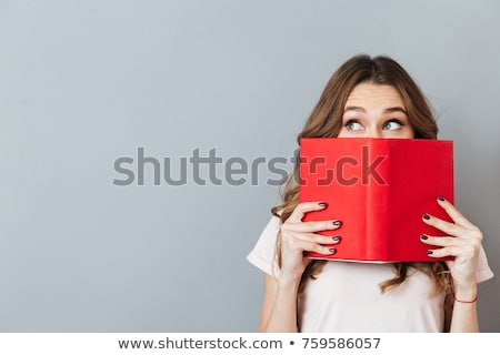 Young happy woman standing with book on gray background Stock photo © deandrobot