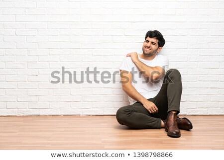 Handsome man having shoulder pain Stock photo © deandrobot
