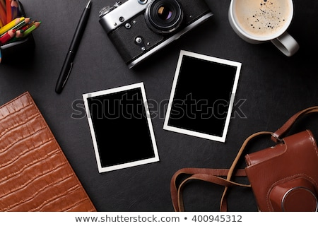 Office desk with photos, camera, coffee and notepad Stock photo © karandaev