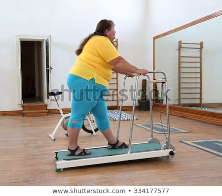 overweight woman running on trainer treadmill Stock photo © Mikko