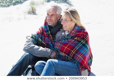 mature couple on beach wrapped in blanket stock photo © is2
