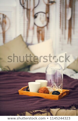 Two white mugs on a tray on the bed in boho style Stock photo © dashapetrenko