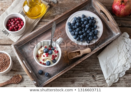 Flax seeds in a bowl, with cottage cheese, oil and blueberries in the background Stock photo © madeleine_steinbach