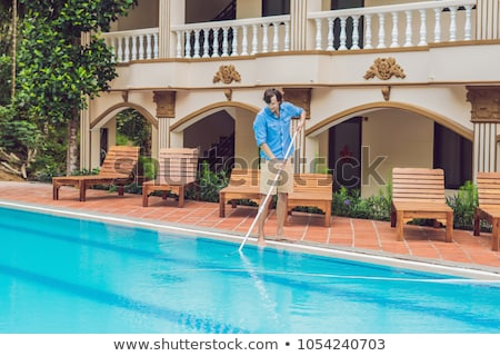 Cleaner of the swimming pool . Man in a blue shirt with cleaning equipment for swimming pools, sunny stock photo © galitskaya