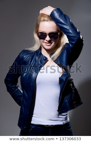 Fashionable girl in sunglasses seductive posing against blue background. Stock photo © studiolucky