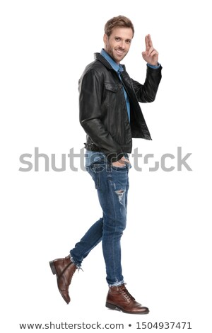 smiling casual man with hand in pocket walks and salutes Stock photo © feedough