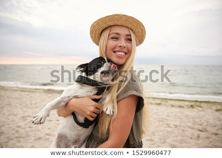 Photo of happy woman 20s wearing black dress and hat holding pre Stock photo © deandrobot