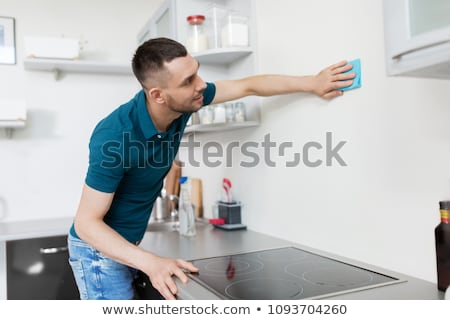 man with rag cleaning wall at home kitchen Stock photo © dolgachov