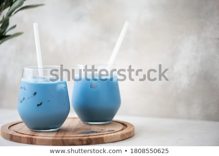 Green tea latte with ice in plastic cup and straw on yellow background. Homemade Iced Matcha Latte T Stockfoto © galitskaya
