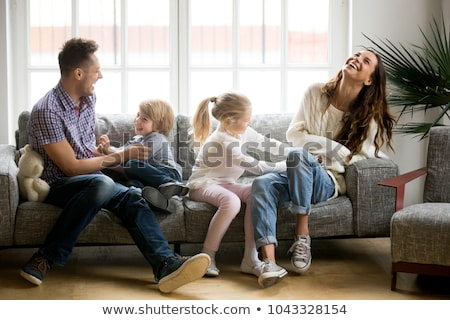 A Family of four having fun on the sofa at home Stock photo © Lopolo