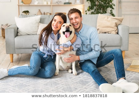 Couple having fun with their pet dog in living room at home Stock photo © wavebreak_media