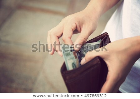 Hands of young woman holding leather wallet with dollar bills and plastic card Stock photo © pressmaster