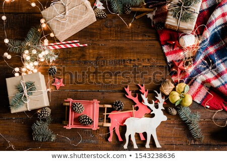 Toy deer and sledge, giftboxes, pine cones, conifer, garlands and decorations Stock photo © pressmaster