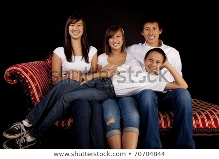 Foto stock: Family Portrait Of Four Siblings In Front Of Black Background