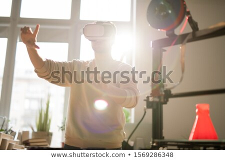 Contemporary guy or office worker in vr headset pointing at virtual screen Stock photo © pressmaster