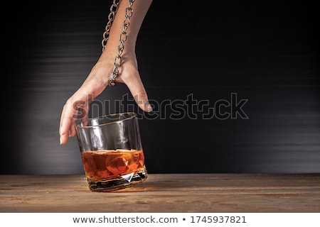 A hand locked to glass of alcohol Stock photo © nomadsoul1