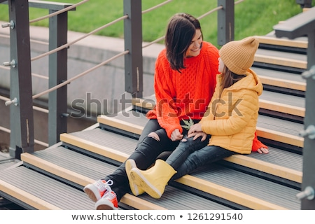 Image of fashionable young woman wears red looe sweater, looks positively at small child, pose toget Stock photo © vkstudio