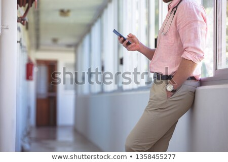 Mid-section of Caucasian male doctor using mobile phone while standing at nursing home corridor Stock photo © wavebreak_media