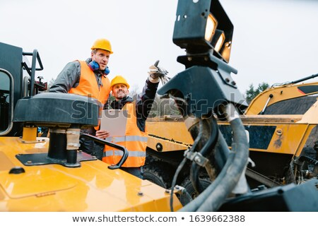 Two male workers on excavator in digging operation or quarry Stock photo © Kzenon