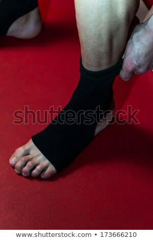 Kick Boxer Putting Straps On His Foot Stock photo © Jasminko