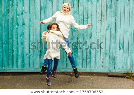 Small fashionable girl and her mother have fun together, keep hands together, pose against brick wal Stock photo © vkstudio
