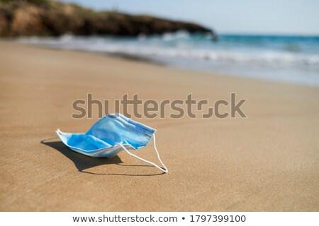 Utilizado mascarilla quirúrgica arena playa primer plano azul Foto stock © nito