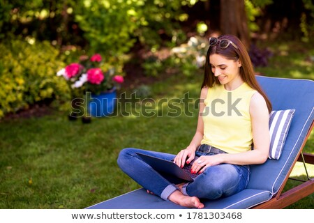 Cute woman sitting on sunbed and smiling Stock photo © dash