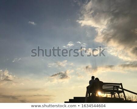 Silhouet vrouw vergadering ontspannen oranje zonsondergang Stockfoto © premiere