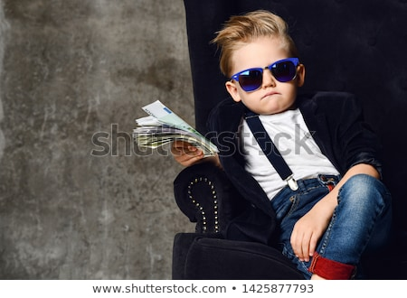 boy sitting on money stock photo © artush