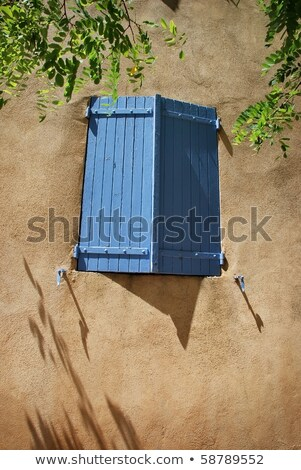 Stock photo: Lavender blue colored shutters on yellow stucco