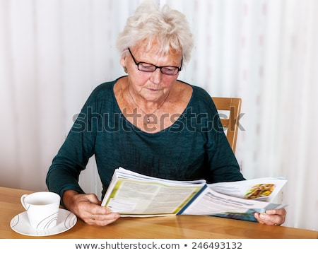 elderly attractive woman reading at home in a magazine stock photo © meinzahn