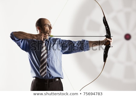 Stock photo: Bowman aiming with a bow and arrow at the target.