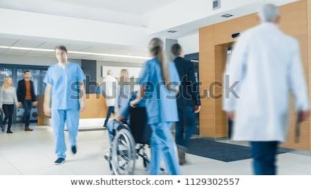 Female nurse assisting patient on wheelchair in corridor Stock photo © wavebreak_media