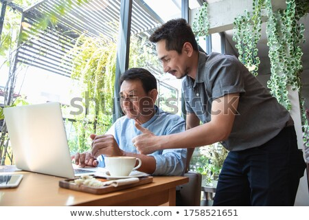 happy elderly couple sitting in cafe and watching in digital screen vector isolated illustration stock photo © pikepicture