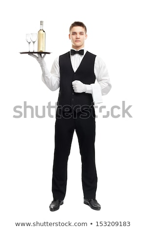 Portrait of a smiling young waiter in tuxedo holding tray Stock photo © deandrobot