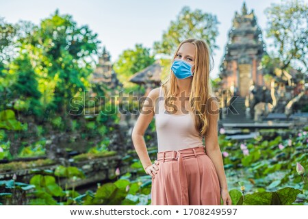 Young woman traveler in the background of Pura Taman Kemuda Saraswati Temple in Ubud, Bali island, I Stock photo © galitskaya