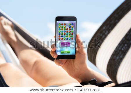 Mujer hamaca jugando videojuegos teléfono móvil cielo azul Foto stock © AndreyPopov