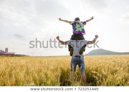 young father with his little son walking in the wheat field at sunset in a warm summer day Stock photo © Lopolo