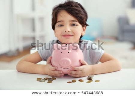 little boy putting coin into piggy bank at home Stock photo © dolgachov
