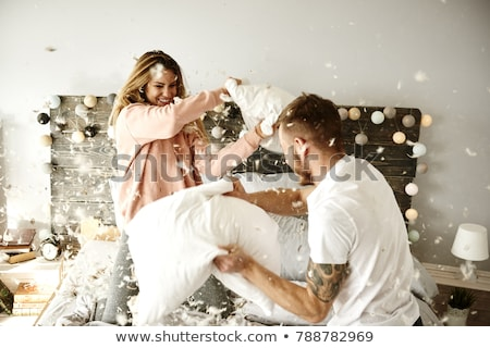 Playful young couple having pillow fight on bed at home Stock photo © boggy