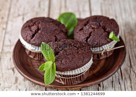 Three chocolate dark muffins with mint leaves on brown ceramic p Stock photo © marylooo
