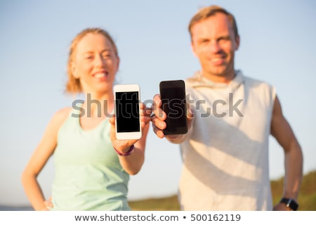 couple with phones and arm bands running on beach stock photo © dolgachov