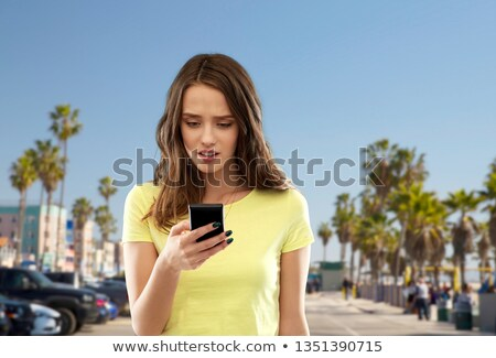 teenage girl using smartphone over venice beach Stock photo © dolgachov