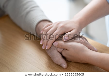 Hand of young affectionate and careful woman on that of her senior father Stock photo © pressmaster