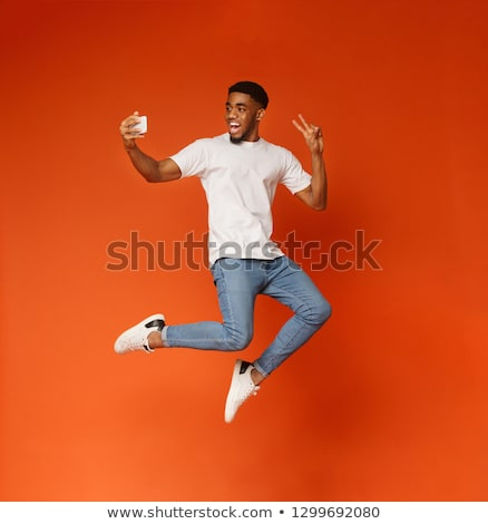 Image of happy african american guy smiling and showing peace si Stock photo © deandrobot