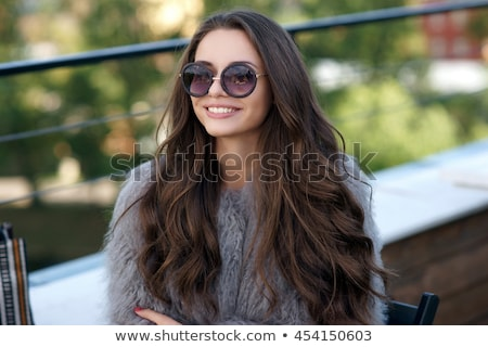 Thoughtful fashionable beautiful woman with long hair and attractive appearance stands against big b Stock photo © vkstudio