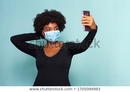 Woman wearing corona mask making selfie with phone Stock photo © Kzenon