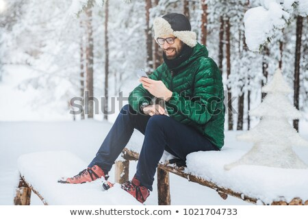 Smiling positive male wears warm winter clothes, reads message on mobile phone, spends free time in  Stock photo © vkstudio