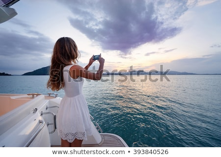 Girl with camera at the sea. Stock photo © Massonforstock